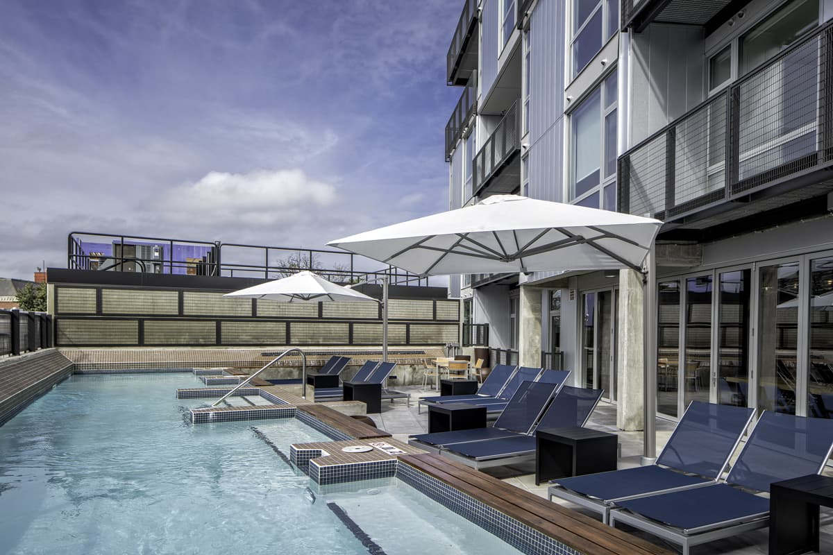 "Amenities include a swimming pool and expansive sun deck, outdoor ""living rooms"" with grilling stations and outdoor kitchens, and a resident lounge with a kitchen, bar, private dining room, pool table, and media center."